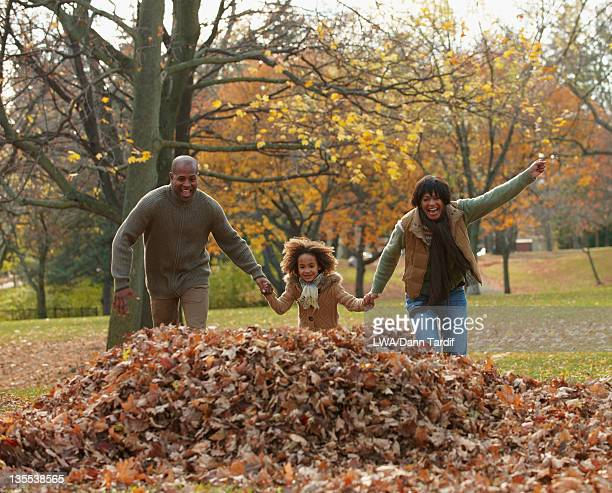 Black family playing in pile of autumn leaves