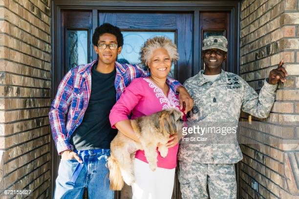 Black family posing with dog in doorway