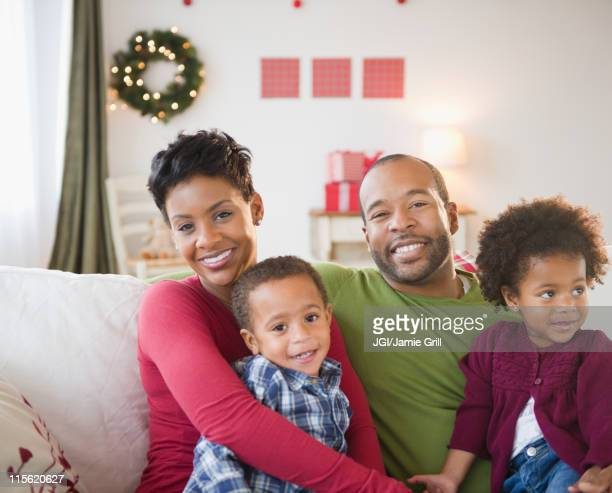 Black family relaxing on sofa together