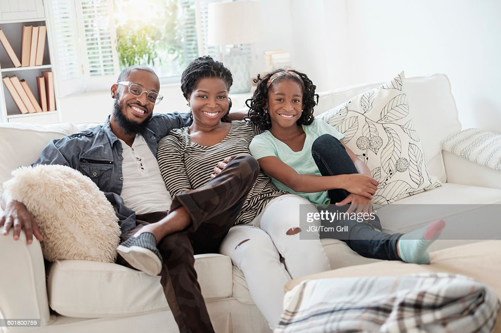 Black Family Smiling On Sofa : Stock Photo