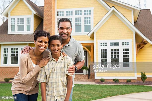 Black family smiling outside home