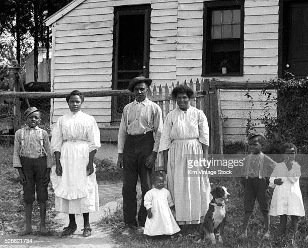 Black family stands in front of their home in the early 20th century.