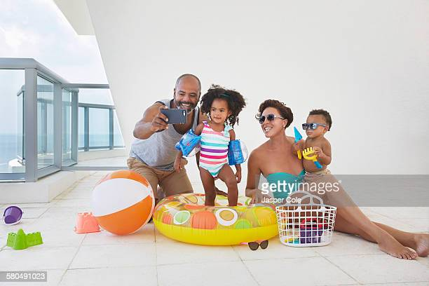 Black family taking selfie with swimming gear