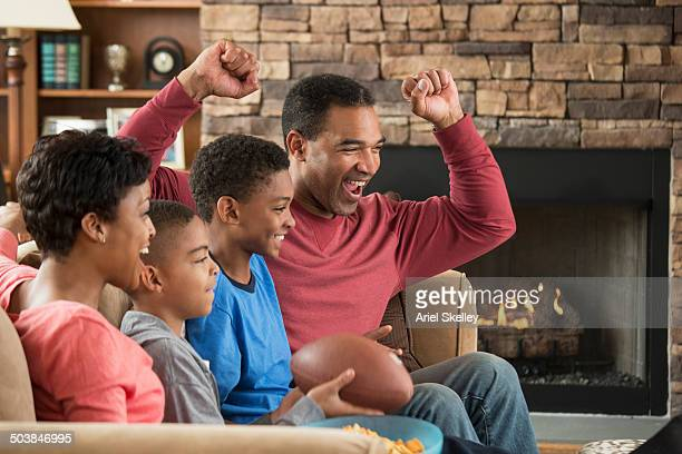 Black family watching sports in living room