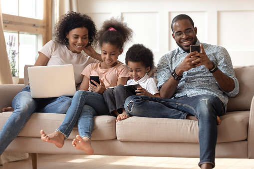 Black family with kids relax on couch using gadgets 1166111243