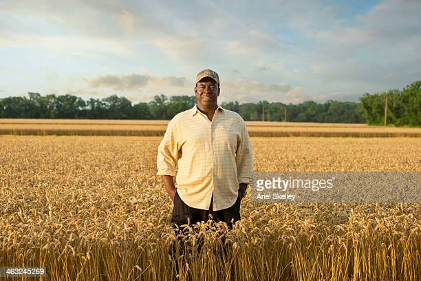 Black farmer standing in wheat field