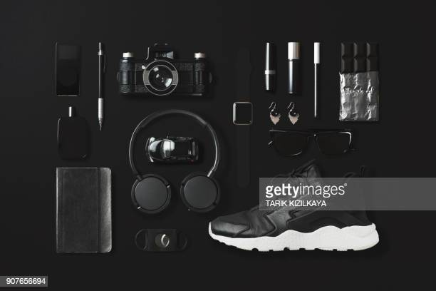 black fashion and technology items flat lay on black background - black shoe stock pictures, royalty-free photos & images