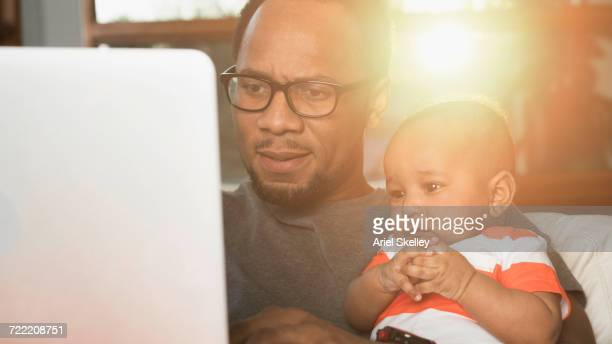 Black father and baby son using laptop