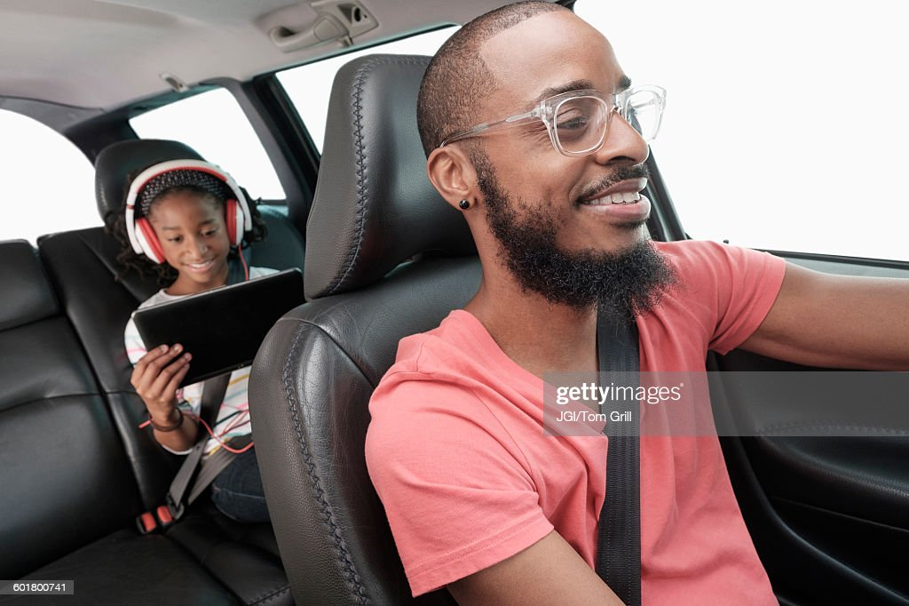 Black father and daughter driving in car : Stock Photo