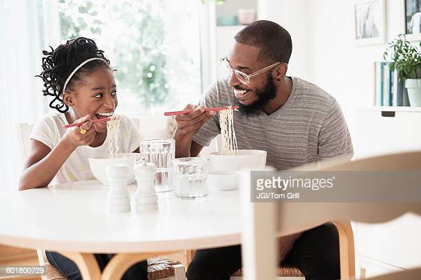 Black father and daughter eating noodles