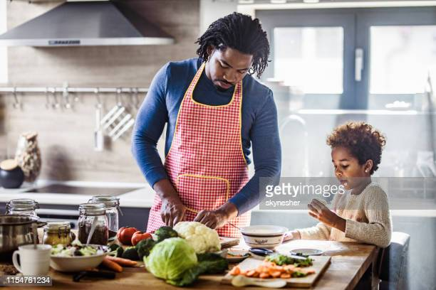 black father and daughter preparing healthy lunch in the kitchen. - cooking stock pictures, royalty-free photos & images