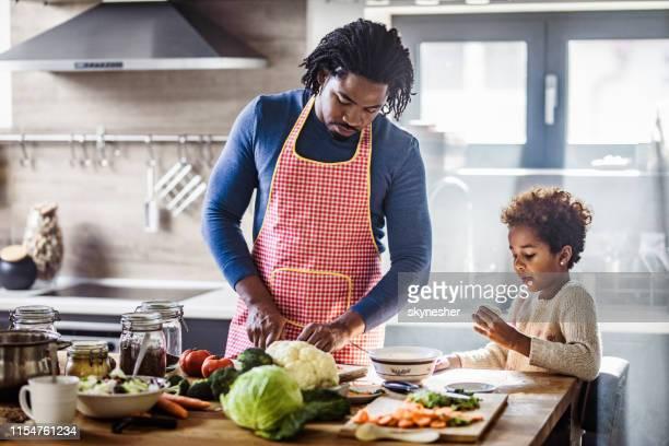 padre negro e hija preparando un almuerzo saludable en la cocina. - black cook fotografías e imágenes de stock