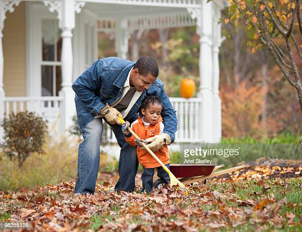 Black father and daughter raking leaves