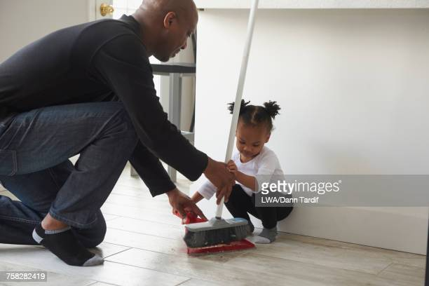 Black father and daughter using broom and dustpan