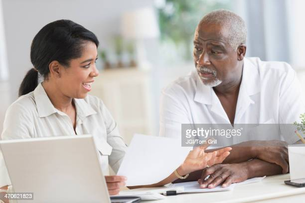 Black father and daughter using laptop