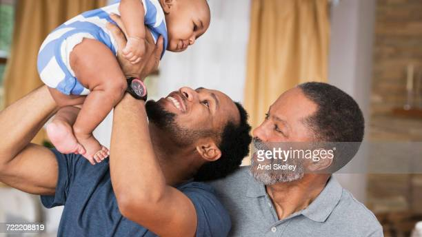 Black father and grandfather playing with baby boy