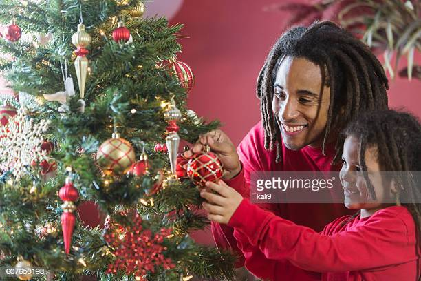 Black father and son decorating Christmas tree