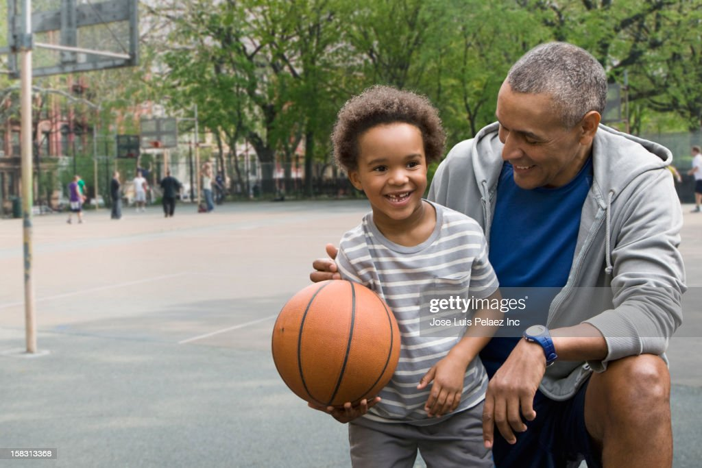Black father and son playing basketball : Stock Photo