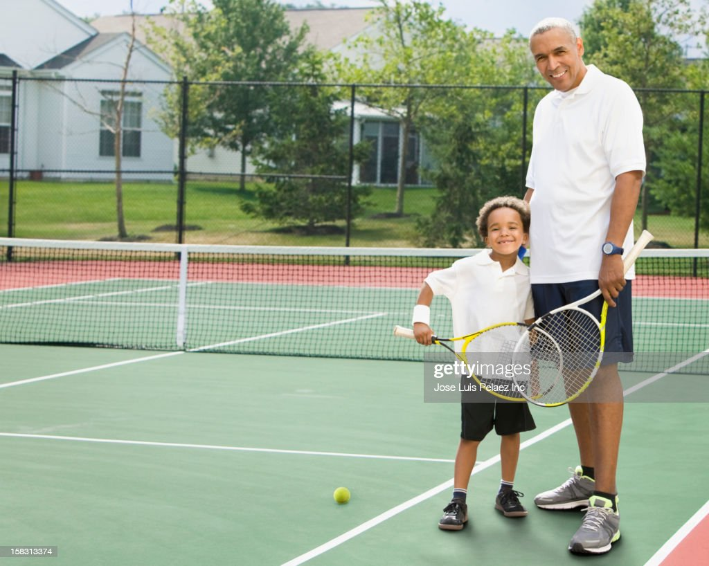 Black father and son playing tennis : Stock Photo