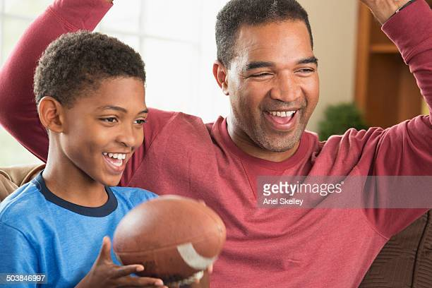 Black father and son watching sports in living room