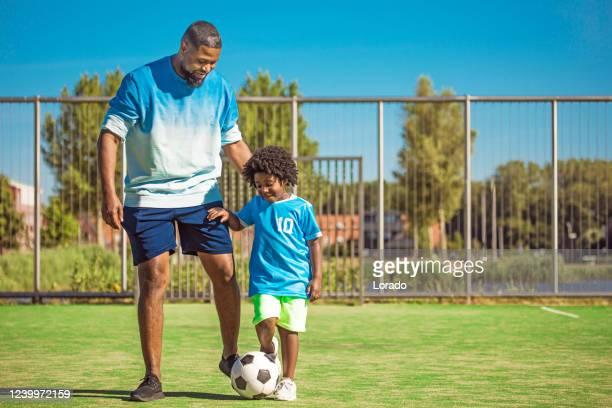 pai negro e filho jovem treinando no campo de futebol - sporting term - fotografias e filmes do acervo