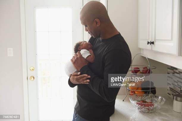 Black father carrying sleeping baby son in domestic kitchen