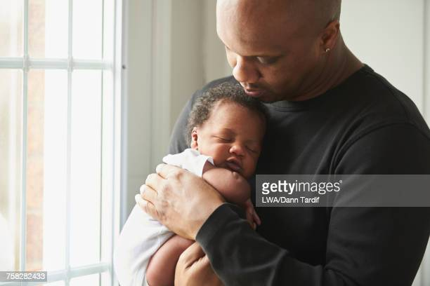 Black father carrying sleeping baby son near window