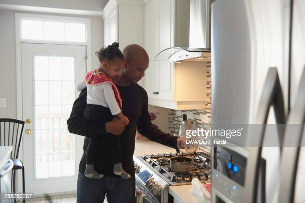 Black father cooking and carrying daughter