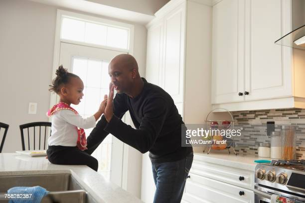 Black father high-fiving daughter