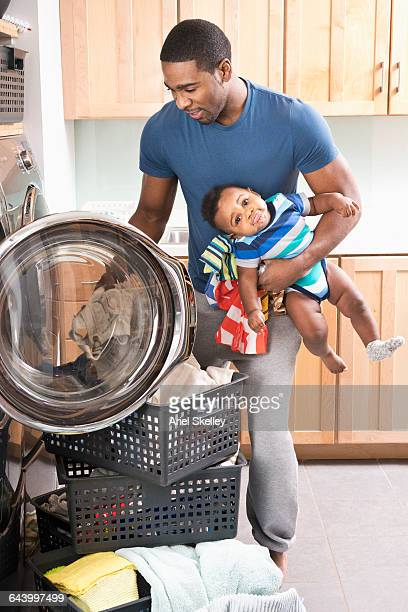 Black father holding baby son and doing laundry