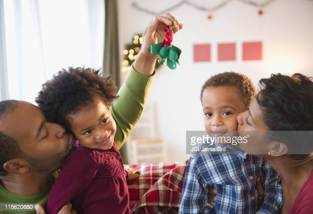black father holding mistletoe over daughter's head - mistletoe stock photos and pictures