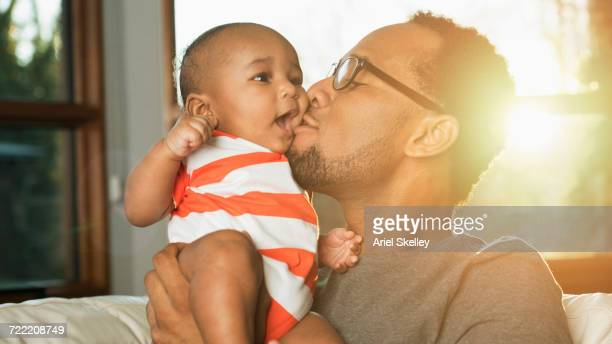 black father kissing baby son on cheek - african american family home stock photos and pictures