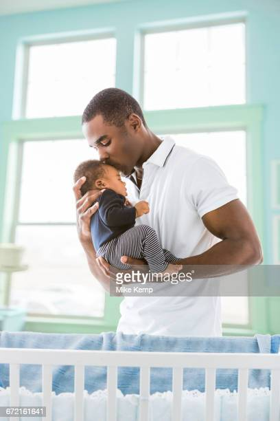 black father kissing baby son on forehead - black man holding baby stock photos and pictures