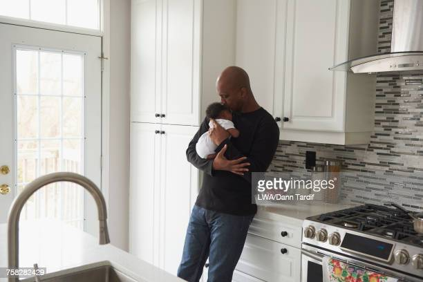 Black father kissing sleeping baby son in domestic kitchen