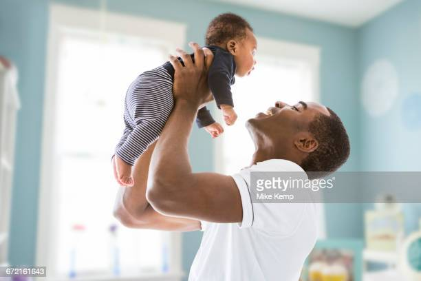 black father lifting baby son - african american family home stock photos and pictures