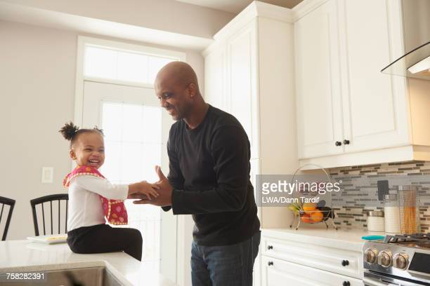 Black father playing hand game with daughter