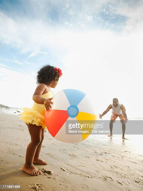 Black father throwing ball on beach with daughter