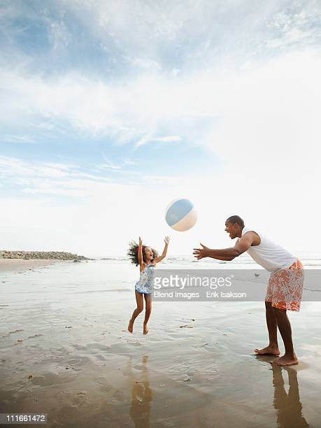 black father throwing ball on beach with daughter - leap day stock pictures, royalty-free photos & images
