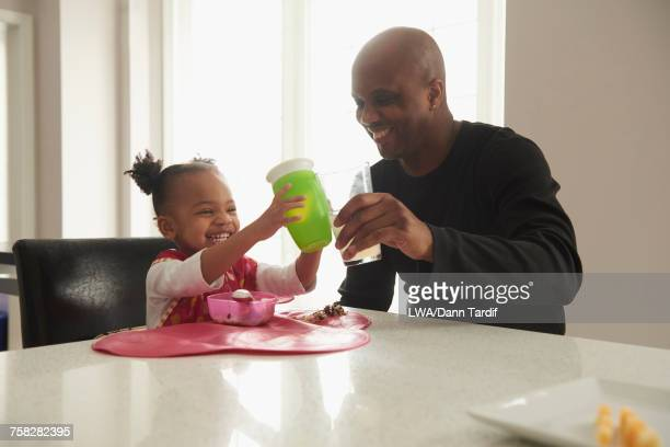 Black father toasting with baby daughter