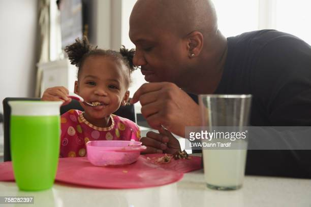 Black father watching baby daughter eating from bowl