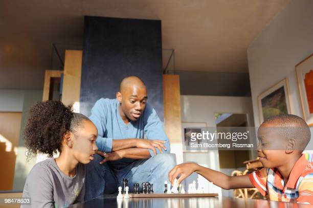 black father watching children play chess - game night leisure activity stock pictures, royalty-free photos & images