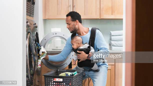 black father with son in baby carrier doing laundry - african american family home stock photos and pictures