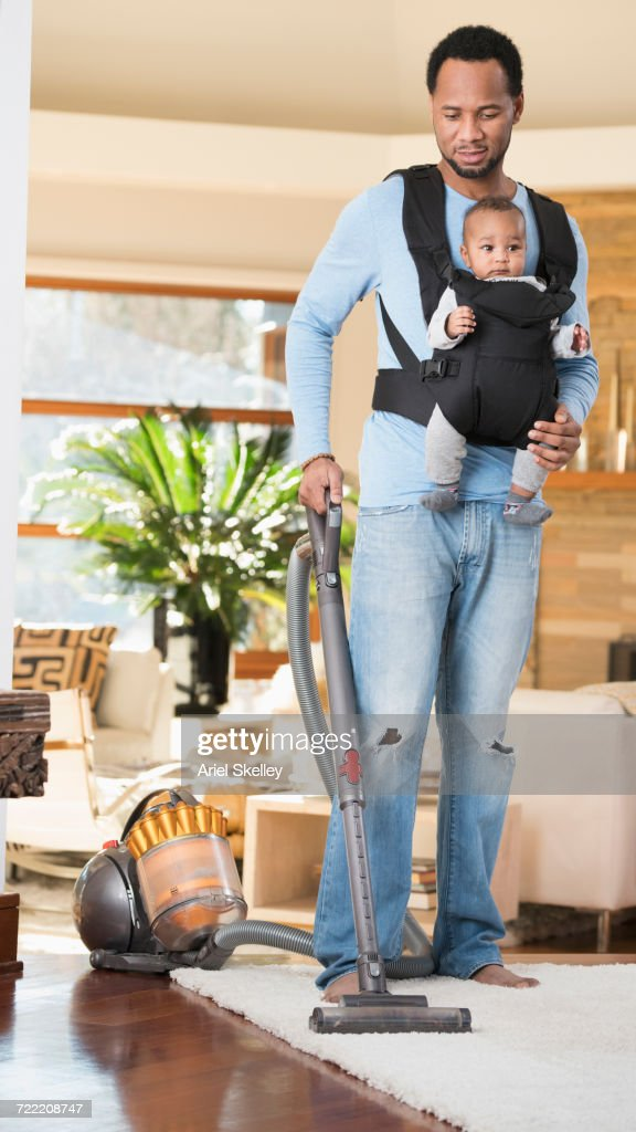 Black Father With Son In Baby Carrier Vacuuming Rug Stock Photo