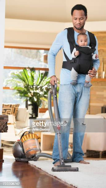 black father with son in baby carrier vacuuming rug - black man holding baby stock photos and pictures
