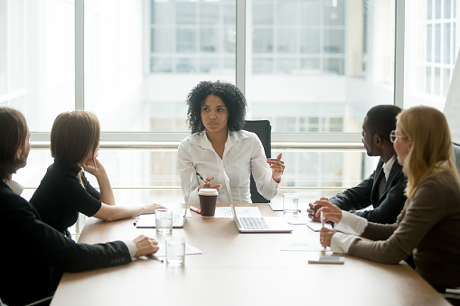 Black female boss leading corporate meeting talking to diverse businesspeople 923039680