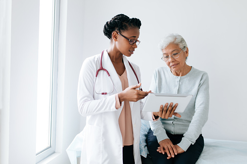 Black female doctor showing digital tablet to senior patient 1094389542