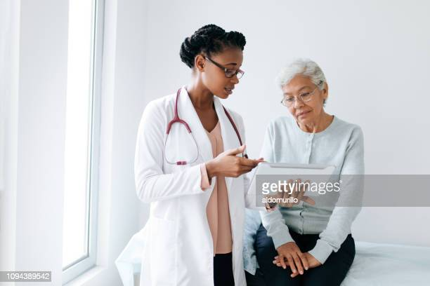 black female doctor showing digital tablet to senior patient - doctor stock pictures, royalty-free photos & images