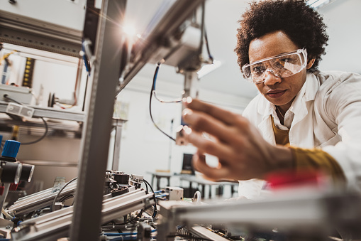 Black female engineer working on industrial machine in a laboratory. 1127076087