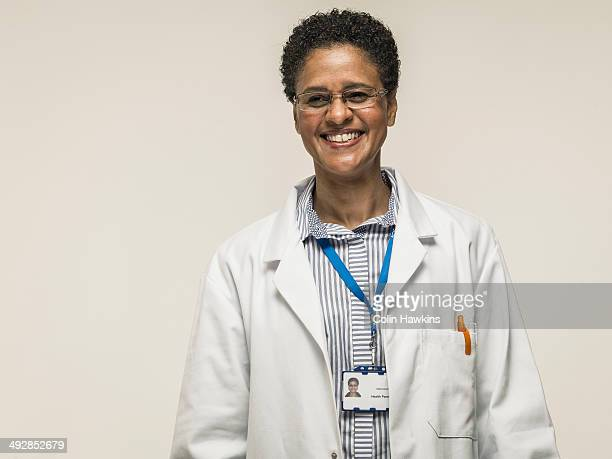 black female in laboratory coat - beige background stock pictures, royalty-free photos & images