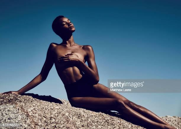 Black female posing on rock.